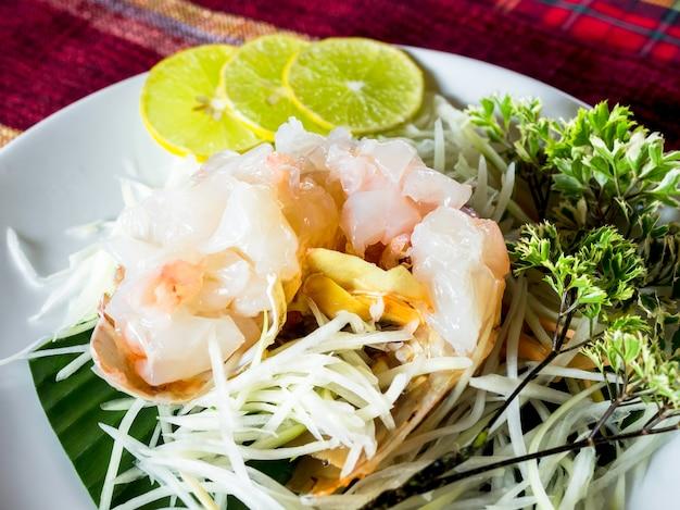Sashimi-hummer, japanisches essen. frischer roher hummer mit geschnittener zitrone auf weißem teller.