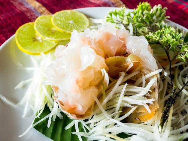 Sashimi-hummer, japanisches essen. nahaufnahme von frischem rohem hummer mit zitronenscheiben auf weißem teller.
