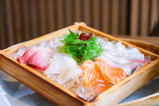 Sashimi-lachs-salat mit japanischer küche und sashimi-salat mit rohem fisch auf eis, serviert auf einem holztablett im japanischen restaurant /