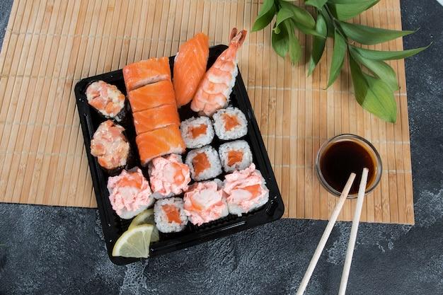Sashimi rollt auf einem schwarzen steinschlag