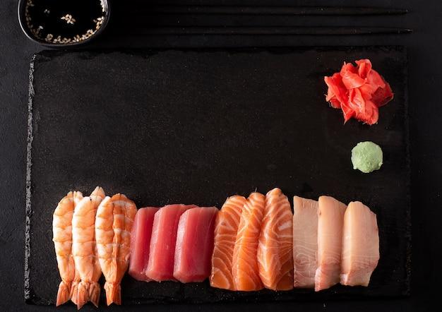 Sashimi-set aus lachs, garnelen, thunfisch und aal auf einer tafel