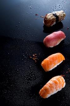 Sashimi, uramaki und nigiri mit reis, lachs oder thunfisch, garnelen in schwarz mit wassertropfen