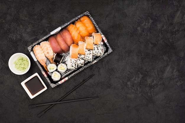 Sashimisushi stellten mit sojabohnenöl und wasabi auf schwarzem hintergrund ein