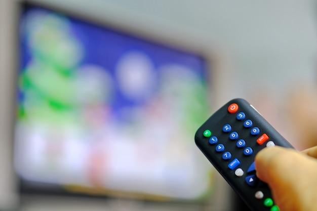 Satellitenempfänger der fernbedienung, der für änderungskanal in der hand hält