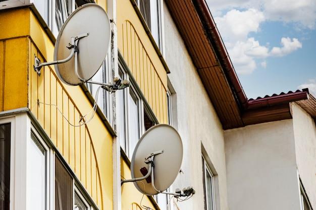 Satellitenschüsseln an der fassade eines mehrstöckigen wohnhauses. satelliten-tv und kommunikation. installation von satellitenanlagen.