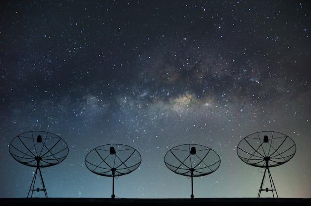 Satellitenschüsseln auf gebäude für telekommunikation mit milchstraße himmel hintergrund