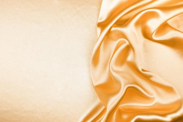 Satin-zusammenfassungshintergrund der goldenen silk beschaffenheit luxuriöser, gewebe