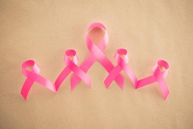 Satinrosa bänder auf dem hellbraunen papier, stützendes symbol des brustkrebsbewusstseins