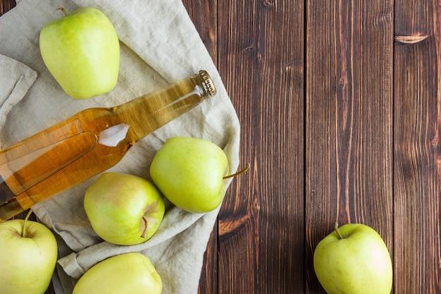 Satz apfelsaft und grüne äpfel auf einem stoff und holzhintergrund. flach liegen. platz für text