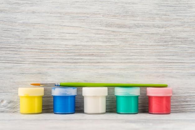 Satz aquarellfarben in den flaschen und in der bürste auf einem weißen hölzernen hintergrund