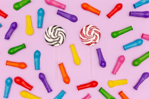 Satz ballone und lutscher auf purpurrotem hintergrund