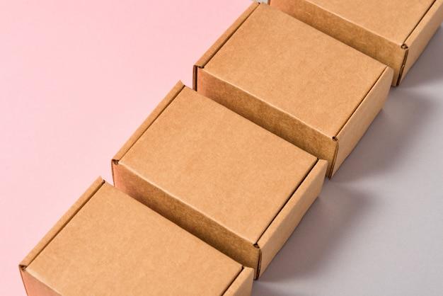 Satz braune pappkartons auf rosa und grauem hintergrund