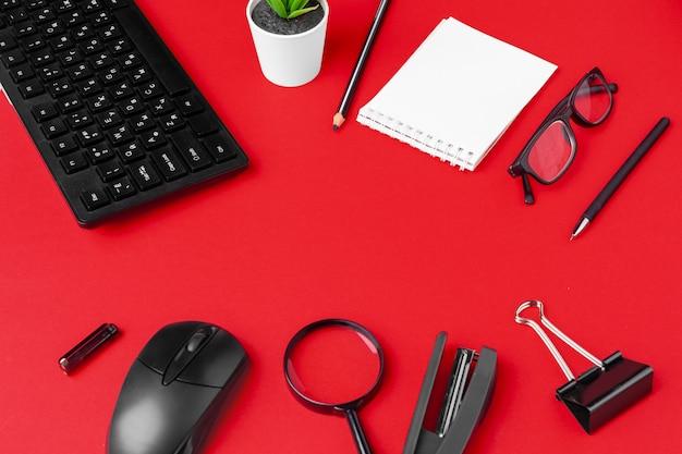 Satz briefpapiereinzelteile auf rotem schreibtisch