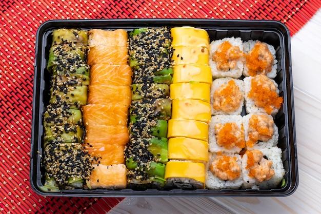 Satz brötchensushi mit lachs im schwarzen tablett. ein japanisches gericht mit meeresfrüchten.
