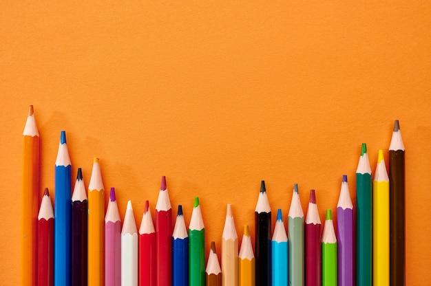 Satz bunte bleistift-nahaufnahme, orange hintergrund. büromaterial, schul- oder bildungszubehör, schreib- und zeichenwerkzeuge