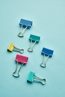 Satz bunte clips auf blauem hintergrund. büromaterial, schul- oder bildungszubehör, schreib- und zeichenwerkzeuge