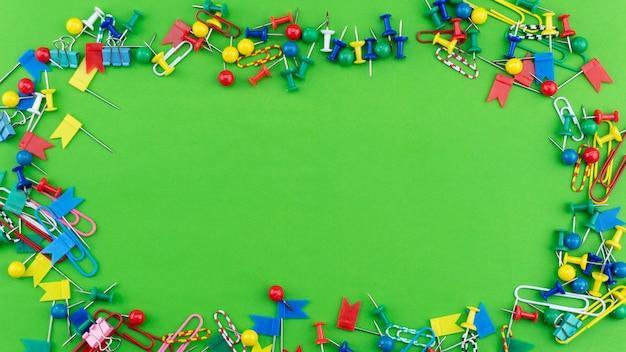 Satz bunte farbstoßstifte thumbtacks gestalten die draufsicht, die auf grünem hintergrund lokalisiert wird