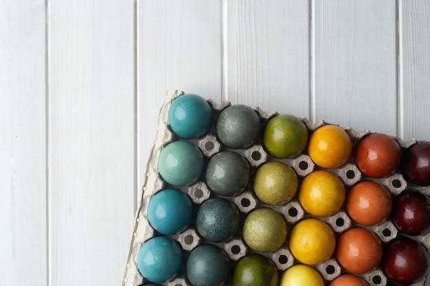 Satz bunte ostereier gefärbt mit natürlichem farbstoff - kurkuma, zwiebelschale, karkade, rotkohl und kaffee in pappe auf weißem hölzernem hintergrund. gradient