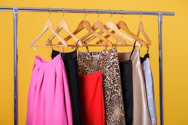Satz bunte röcke der frauen auf hölzernen kleiderbügeln auf gestell auf orange hintergrund. sommergarderobe von frauen