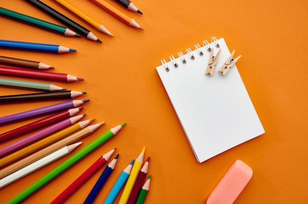 Satz bunte stifte und notizblock, orange hintergrund. büromaterial, schul- oder bildungszubehör, schreib- und zeichenwerkzeuge