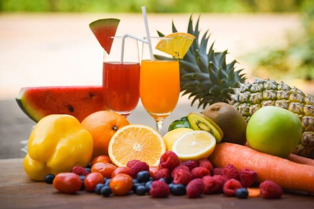 Satz bunte und frische sommersaftglas der tropischen früchte gesunde / viele reife frucht gemischt