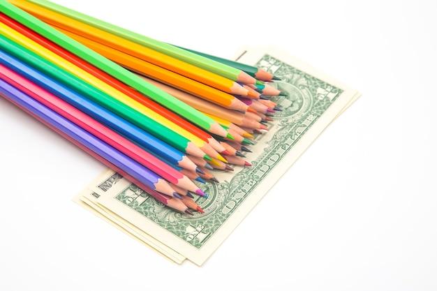 Satz buntstifte zum zeichnen auf einem dollarhintergrund.