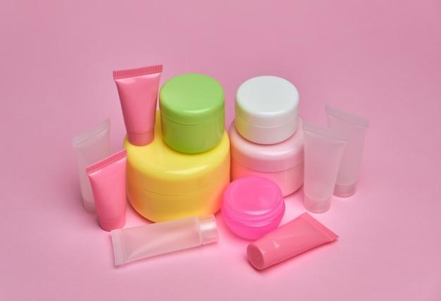 Satz cremebehälter und -röhrchen auf rosa oberfläche