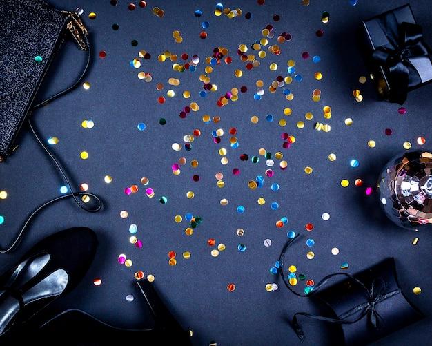 Satz damenaccessoires für party- und goldbuntkonfetti auf schwarzer oberfläche