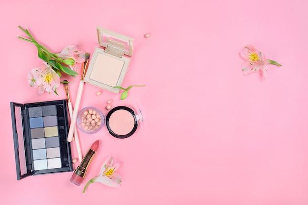 Satz dekorative kosmetik mit make-up-pinseln auf rosa hintergrund