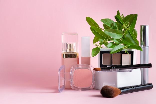 Satz dekorative kosmetik und make-up-pinsel auf rosa hintergrund.