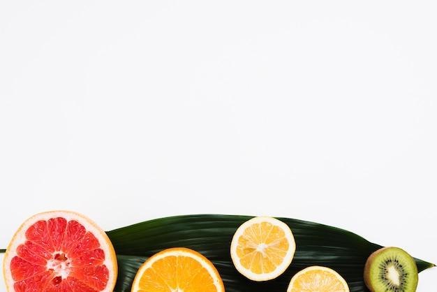 Satz der hälfte der tropischen früchte auf bananenblatt auf weißem hintergrund