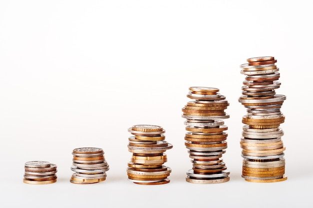 Satz der spalte fünf der verschiedenen münzen, die in folge auf weißem hintergrund bleiben. kann als symbol für vermögenszuwachs oder geld-diagramm verwendet werden.