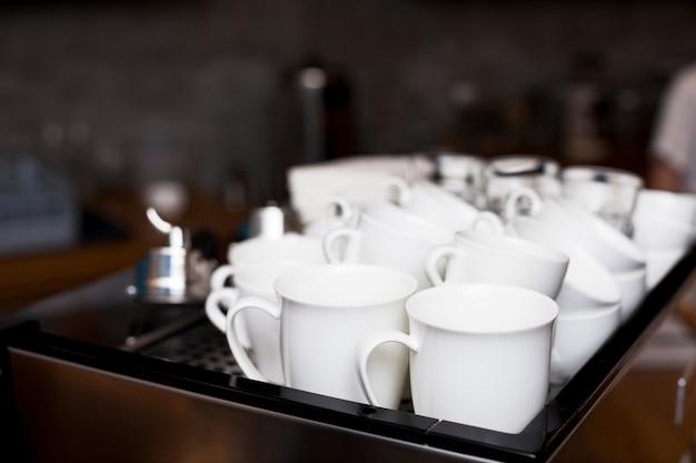 Satz der weißen kaffeetasse auf behälter in der cafeteria
