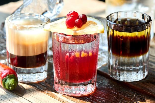 Satz des alkoholischen cocktails bestehend aus b-52, dem schüler eines nazis und boyarsky in den gläsern auf einem holztisch