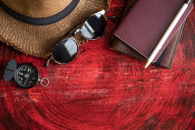 Satz des passes, des notizbuches, der sonnenbrille, des kompasses und des weißen bleistifts auf tabelle
