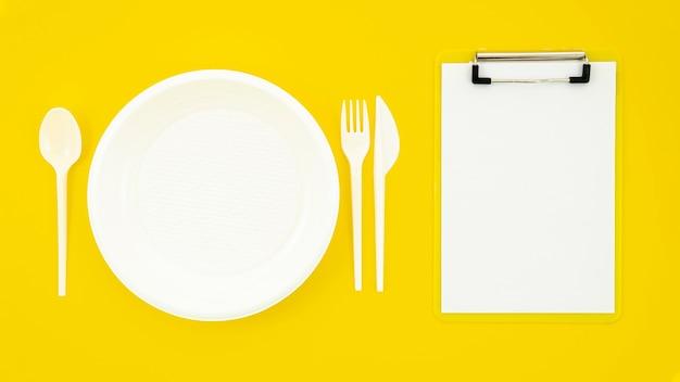 Satz des weißen tellers und des klemmbrettes auf gelbem hintergrund