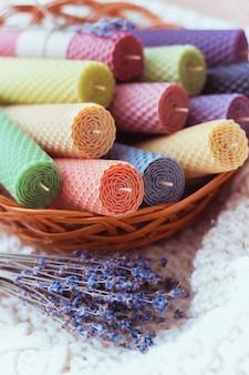 Satz farbige dekorative natürliche bienenwachskerzen mit einem honigaroma für innenraum in einem braunen korb nahe lavendel auf einem weißen strickpullover