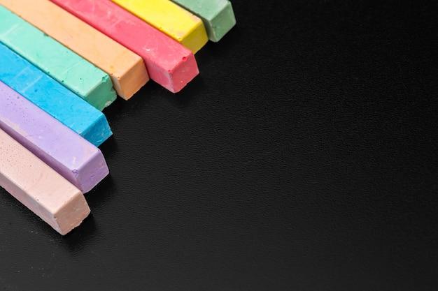Satz farbige kreiden über einem schwarzen hintergrund
