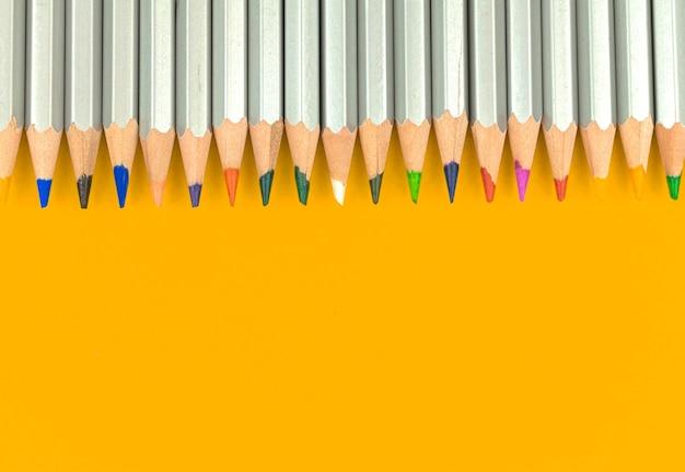 Satz farbstifte in grenzkomposition. gelber desktop-hintergrund. platz kopieren und foto flach legen