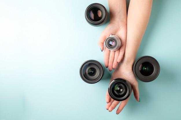 Satz fotoobjektive auf einem farbigen hintergrund, die auswahl und der vergleich der fotoausrüstung, hände halten fotoausrüstung
