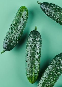 Satz frische ganze gurken auf grünem hintergrund, lebensmittelmuster. gartengurkentapete hintergrunddesign