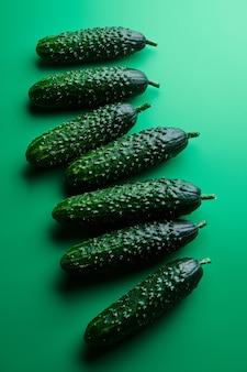 Satz frische ganze gurken lokalisiert auf einem grünen hintergrund, freistellungspfad. gartengurkentapete hintergrunddesign