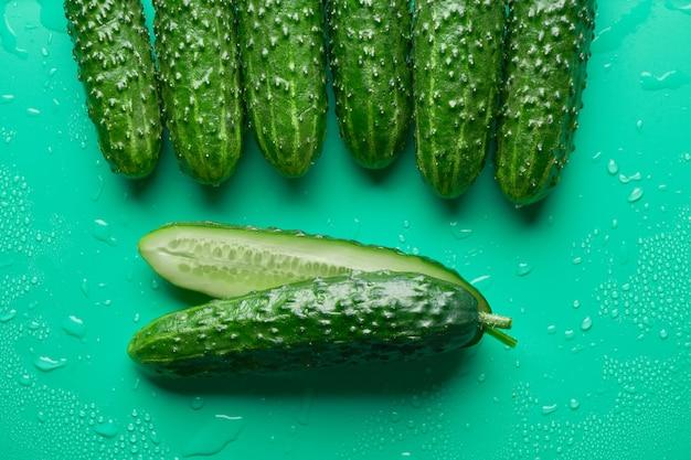 Satz frische ganze und geschnittene gurken auf grünem hintergrund mit wassertropfen. gartengurkentapete hintergrunddesign