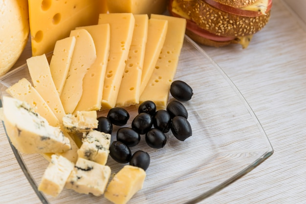 Satz frischkäse und oliven auf teller nahe sandwich