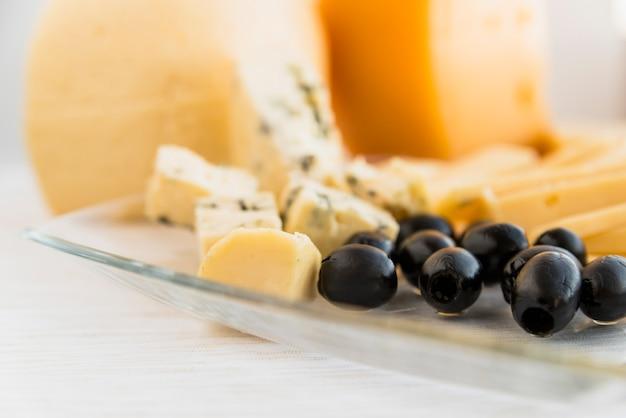 Satz frischkäse und oliven auf teller