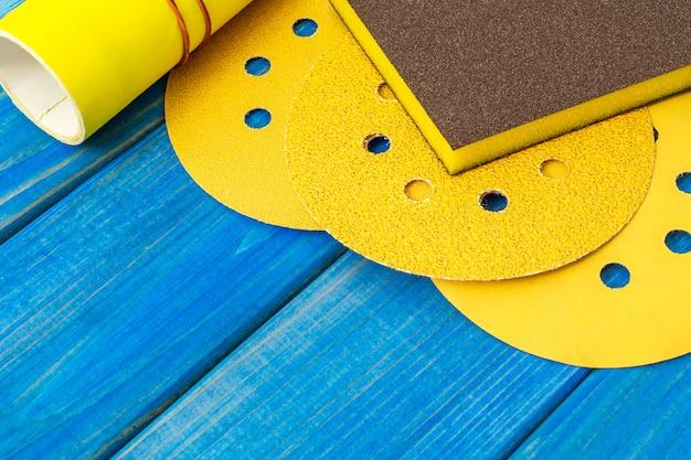 Satz gelbe schleifwerkzeuge und schleifpapier auf blauen holzbrettern