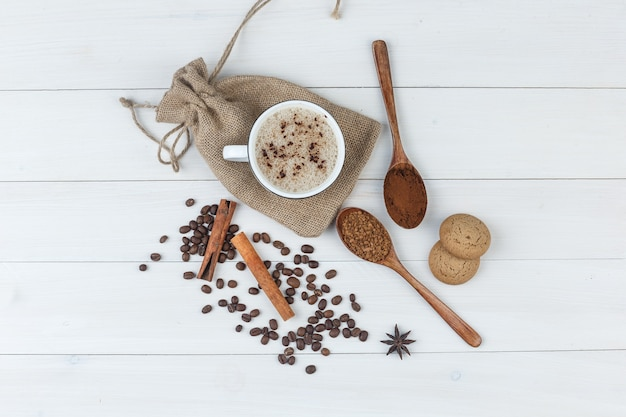 Satz gemahlener kaffee, gewürze, kaffeebohnen, kekse und kaffee in einer tasse auf hölzernem und sackhintergrund. draufsicht.