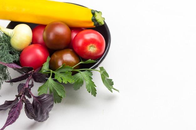 Satz gemüse und zweige basilikum und petersilie in schwarzer schüssel. gelbe zucchini und rote tomaten. weißer hintergrund. platz kopieren. ansicht von oben