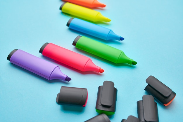 Satz geöffneter bunter bleibender markierungen auf blauem hintergrund. büromaterial, schul- oder bildungszubehör, schreib- und zeichenwerkzeuge