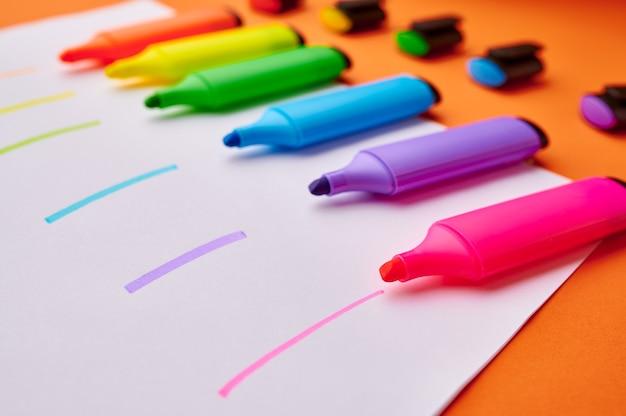 Satz geöffneter bunter dauerhafter markierungen auf papierblatt mit strichen. büromaterial, schul- oder bildungszubehör, schreib- und zeichenwerkzeuge